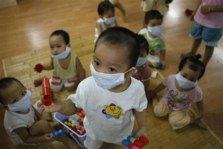 Children wear protective masks at a kindergarten in Hanoi August 7, 2009. REUTERS/Kham