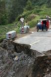 """<p>Люди ждут на обочине дороги, разрушенной тайфуном """"Саомай"""" недалеко от китайского города Цаннань 11 августа 2006 года. 11 августа 2006 года сильнейший тайфун """"Саомай"""" обрушился на китайскую восточную провинцию Чжэцзян, унеся жизни более 319 человек. """"Саомай"""" стал самым сильным ураганом в истории Китая за последние 50 лет. REUTERS/ Nir Elias</p>"""