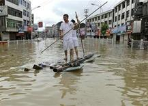<p>Люди проплывают наулицах на самодельных плотах, после того как тайфун Моракот обрушился на город Вэньчжоу, китайская провинция Чжэцзян 1- августа 2009 года. Вертолеты спасателей кружат над деревней Гаосюн на острове Тайвань, где под селевым потоком после тайфуна погребено предположительно 600 человек. REUTERS/Lang Lang</p>