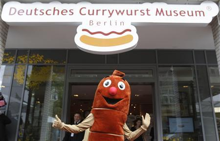 A person dressed as a curry wurst mascot, poses outside the entrance to the newly opened Curry Wurst Museum in Berlin, August 13, 2009. Curry Wurst is a German national dish that consists of a hot pork sausage seasoned with tomato ketchup and curry powder, and served with chips or bread rolls. REUTERS/Tobias Schwarz