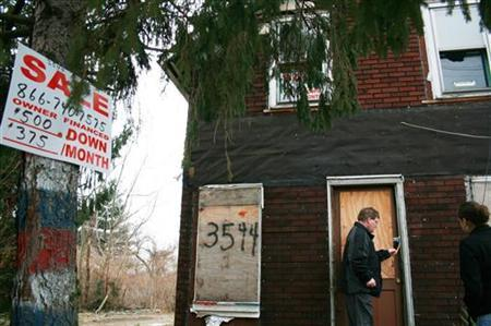 Mark Seifert (L), and Lindsey Sacher (R), of the non-profit group East Side Organizing Project (ESOP), approach a home in the Cleveland, Ohio neighborhood of Slavic Village in this picture taken February 8, 2008. REUTERS/Nick Carey