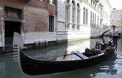 <p>Tourists sit in a gondola as they travel through a canal in Venice, May 8, 2009. REUTERS/Stefano Rellandini</p>