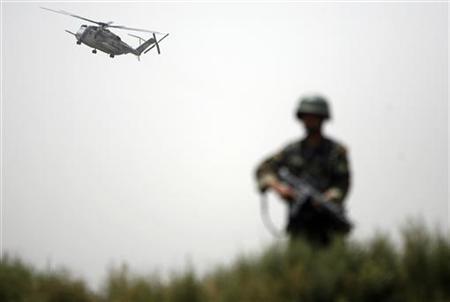 An Afghan National army soldier keeps watch as a U.S. marine helicopter flies overhead in Khan Neshin district of Helmand province July 8, 2009. U.S. REUTERS/Ahmad Masood