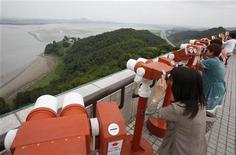 <p>Люди смотрят на деревню в Северной Корее с наблюдательной площадки в Пхаджу 17 августа 2009 года. Северная Корея сообщила в понедельник о намерении открыть границу с Южной Кореей, закрытую девять месяцев назад по инициативе Пхеньяна. REUTERS/Jo Yong-Hak</p>