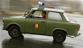 <p>A Trabant car from the National People's Army (NVA) of the former GDR drives during a fan meeting at the 50th anniversary of the Trabant car in Zwickau November 10, 2007. REUTERS/Hannibal Hanschke</p>