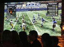 <p>Game 'Madden NFL '09 é projetado em parede em lançamento em Los Angeles. Com as produtoras de videogames chegando próximas da perfeição na reprodução do visual das superfícies em que jogos são disputados, o próximo passo para aumentar o realismo seria reproduzir o clima real, seja em um estádio de futebol ou pista de golfe, que influencia a aparência do jogo e o desempenho dos jogadores.</p>