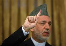 <p>Afghan President Hamid Karzai holds up his inked stained finger as he gestures during a news conference on election day in Kabul August 20, 2009. REUTERS/Ahmad Masood</p>