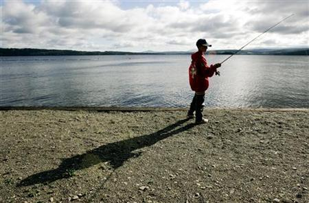 Eleven year-old Matthew English from New Jersey fishes on the shores of Rangeley Lake, which is being monitored for mercury levels, in Rangeley, Maine, August 23, 2005. REUTERS/Brian Snyder