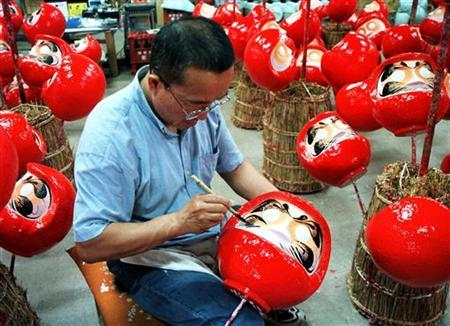 A Japanese craftsman adds the final touches to a daruma doll in Takasaki. REUTERS/file