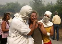 <p>Il pianto di una donna che evacuata dalla sua casa minacciata dalle fiamme ad Anthousa, sobborgo a nord di Atene. REUTERS/Yiorgos Karahalis (GREECE DISASTER ENVIRONMENT)</p>