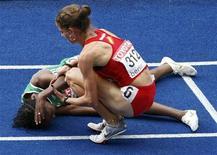 <p>Natalia Rodríguez consola a etíope Gelete Burka após vencer a prova feminina dos 1.500 metros no Mundial de Atletismo de Berlim no domingo. REUTERS/Fabrizio Bensch</p>
