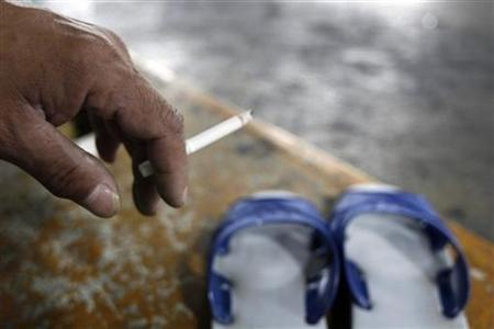 Xie Yung-cheng, 54, smokes a cigarette at his sleeping area inside a carpark in Taiwan, November 21, 2007. REUTERS/Nicky Loh