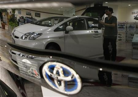 A man looking at a Toyota Motor's Prius hybrid vehicle is reflected on a black Prius at its dealers shop in Yokohama, south of Tokyo August 4, 2009. REUTERS/Toru Hanai