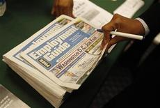 <p>A job seeker picks up a copy of the Washington Job Guide at a job fair in a Washington hotel, August 6, 2009. REUTERS/Jason Reed</p>