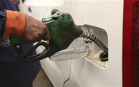 An employee fills a car with petrol at a gas station in Jammu July 1, 2009. REUTERS/Mukesh Gupta