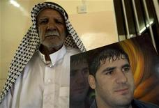 <p>Il padre del giornalista iracheno Ibrahim Jassam con la foto del figlio a Mahmudiya. REUTERS/Thaier al-Sudani (IRAQ CONFLICT POLITICS)</p>