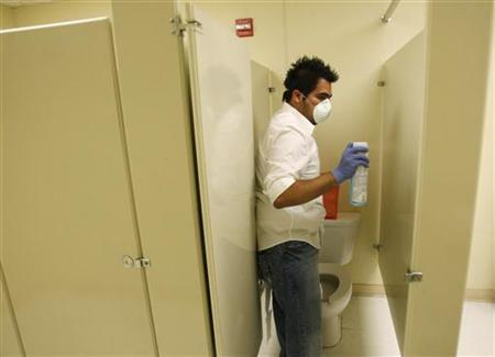 A worker disinfects a bathroom inside the Golden Rule Charter School after a suspected case of swine flu caused the school to close in Dallas, Texas April 29, 2009. REUTERS/Jessica Rinaldi