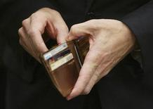 <p>Treasury Secretary Timothy Geithner puts a piece of foreign currency back in his wallet after showing off the contents of his wallet to a photographer during a break in his testimony before the House Appropriations Subcommittee on General Government and Financial Services on Capitol Hill in Washington, May 21, 2009. REUTERS/Jim Bourg</p>