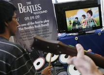"<p>People play ""The Beatles: Rock Band"" game during its launch in New York, September 9, 2009. REUTERS/Shannon Stapleton</p>"