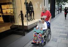 <p>Пожилая женщина с собачкой в инвалидном кресле в Токио 18 июля 2009 года. В Японии живет более 40.000 людей старше 100 лет, это на 10 процентов больше, чем в прошлом году. JAPAN-ELECTION/BIRTHRATE REUTERS/Thomas White/Files</p>