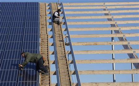 Workers install solar panels on what will be the biggest integrated solar panel roof of the world, at a farm in Weinbourg, Eastern France February 12, 2009. REUTERS/Vincent Kessler