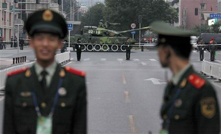 Paramilitary policemen stand guard as a People's Liberation Army (PLA) tank drives past them as they head towards Beijing's Tiananmen Square September 18, 2009, during a rehearsal for the National Day parade. REUTERS/David Gray