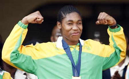 Caster Semenya gestures to a crowd gathered to greet her at the OR Tambo International Airport in Johanneburg August 25 ,2009. REUTERS/Siphiwe Sibeko