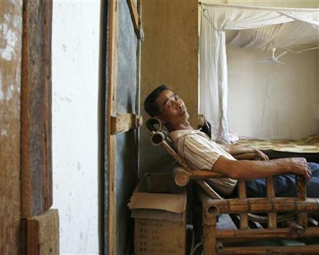 He Kangcai, 60, who is suffering from stomach cancer, poses in his home at Shangba village in the northern part of China's Guangdong province August 27, 2009. REUTERS/Bobby Yip