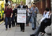 <p>Jobless university graduate David Rowe wears a sandwich board advertising his search for employment as he walks along Fleet Street in central London, September 22, 2009. REUTERS/Kieran Doherty</p>