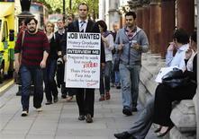 <p>Jobless university graduate David Rowe wears a sandwich board advertising his search for employment as he walks along Fleet Street in central London, September 22, 2009. REUTERS/Kieran Doherty</p>
