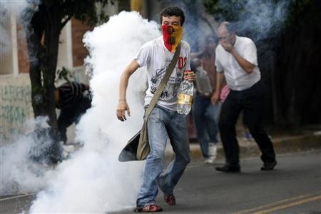 Supporters of ousted Honduras President Manuel Zelaya run amidst tear gas fired by police, near the Brazilian embassy in Tegucigalpa September 22, 2009. REUTERS/Oswaldo Rivas