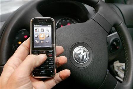 A mobile phone is used in a car in this posed photograph in central London February 27, 2007. REUTERS/Toby Melville
