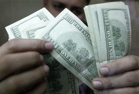 An employee checks dollar bills inside a money changer in Manila August 7, 2009. REUTERS/Cheryl Ravelo
