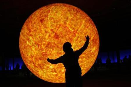 A girl poses in front of a large model of the sun at an exhibition in the Gasometer museum in Oberhausen July 28, 2009. REUTERS/Ina Fassbender