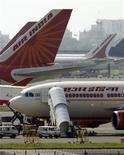 <p>Самолеты Air India в аэропорту Бомбея 27 сентября 2009 года. Терпящая убытки государственная авиакомпания Air India отменила четверть своих международных и местных полетов и приостановит бронирование на большинство рейсов из-за забастовки пилотов, сообщил представитель компании во вторник. REUTERS/Punit Paranjpe</p>