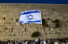 <p>Человек держит израильский флаг в Иерусалиме 21 мая 2009 года. 30 сентября 1980 года Израиль ввел в обращение шекель, денежную единицу, заменившую фунт. REUTERS/Darren Whiteside</p>