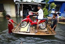 """<p>Жители на самодельном плоту переправляют мотоцикл по заводи, образовавшейся из-за тайфуна """"Кетсана"""", лагуна Сан-Педро,Манила 1 октября 2009 года. Новый """"супер-тайфун"""" может обрушиться на Филиппины спустя всего несколько дней после того, как наводнения унесли жизни почти 300 человек в окрестностях Манилы. REUTERS/John Javellana</p>"""