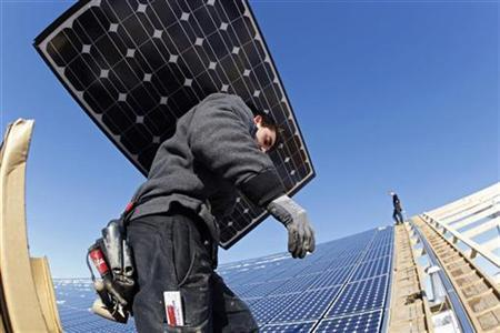 Workers install solar panels on what will be the biggest integrated solar panel roof of the world, at a farm in Weinbourg, Eastern France in this February 12, 2009 file photo. REUTERS/Vincent Kessler