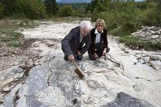 <p>Patrice Landry (L) and Marie-Helene Marcaud, discoverers and members of an amateur science society specialising in geology and paleontology, pose next to well-preserved footprints, between 1.5 and two metres in diameter, in Plagne eastern France October 6, 2009. REUTERS/Robert Pratta</p>