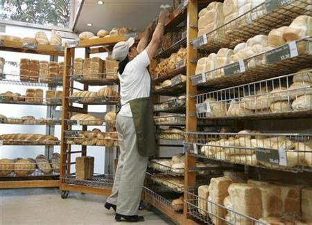 Bakery worker Madhu Govind stocks the shelves in Dee Why, a suburb of northern Sydney April 23, 2008. REUTERS/Will Burgess