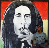 <p>Человек стоит у изображени певца Боба Марли в Кингстоне 12 июля 2001 года. 8 октября 1980 года легендарный певец Боб Марли отыграл последний концерт. Он скончался семь месяцев спустя от рака. REUTERS/Kimberly White</p>