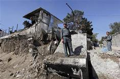 <p>Афганский полицейский на месте взрыва у посольства Индии в Кабуле 8 октября 2009 года. Как минимум семь человек погибли и 45 получили ранения в результате взрыва у посольства Индии в столице Афганистана, сообщили источники в полиции страны. REUTERS/Ahmad Masood</p>