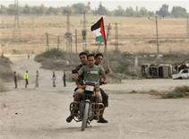 <p>Alcuni palestinesi a bordo di una moto nella Striscia di Gaza. REUTERS/Mohammed Salem</p>