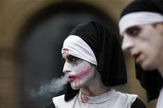"""<p>Два участника парада зомби курят в о Франкфурте-на-Майне 18 июля 2009 года. Текстовые сообщения могут помочь некоторым курильщикам отказаться от вредной привычки или просто служить """"хорошим напоминаем"""" о следовании к намеченной цели, говорится в международном исследовании. REUTERS/Johannes Eisele</p>"""