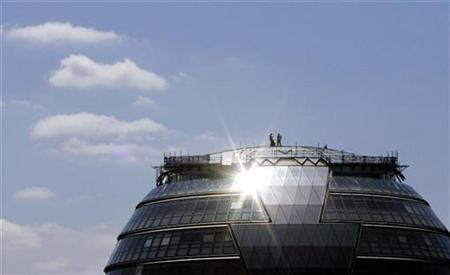 Workers install photovoltaic solar panels on the roof of City Hall in London in this May 23, 2007 file photo. REUTERS/Alessia Pierdomenico