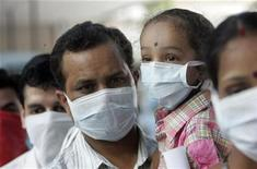 <p>People wearing masks wait in a queue for a H1N1 flu screening at a hospital in New Delhi August 11, 2009. REUTERS/Fayaz Kabli</p>