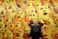 <p>Chinese artist Fang Lijun poses in front of his painting in Taipei in this April 17, 2009 file photo. After a white-hot stint, the financial crisis has battered China's art landscape. REUTERS/Pichi Chuang/Files</p>
