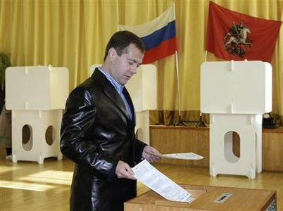 Russian President Dmitry Medvedev drops his ballot into a ballot box at a polling station in Moscow October 11, 2009. REUTERS/RIA Novosti/Kremlin/Vladimir Rodionov
