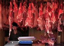 """<p>Человек продает мясо в Урумчи 16 июля 2009 года. Постер движения защитников животных, пропагандирующий вегетарианство, был запрещен Британским агентством рекламных стандартов за ложную информацию, убеждающую потребителей, что употребление мяса приводит к заболеванию """"свиным"""" гриппом. REUTERS/David Gray</p>"""