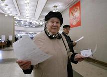 <p>Женщина голосует на выборах в Мосгордуму 11 октября 2009 года. Немногочисленная парламентская оппозиция покинула заседание российской Госдумы в среду, требуя пересмотра результатов выборов в Мосгордуму, над которой партия власти установила полный контроль. REUTERS/Sergei Karpukhin</p>